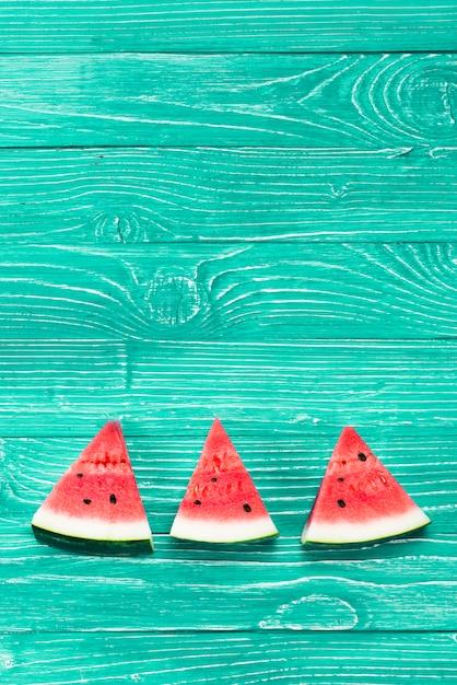 Rote stücke frische wassermelone auf grünem hintergrund Kostenlose Fotos
