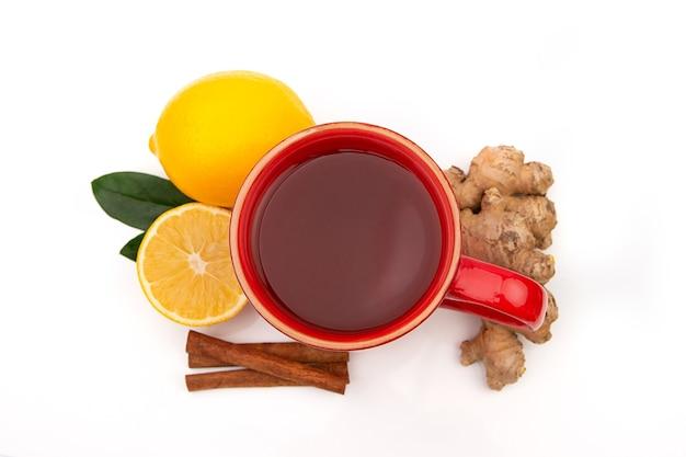 Rote tasse heißen schwarzen oder grünen tees mit zitrone und ingwer auf einem weißen hintergrund. inhaltsstoffe gegen influenza und viren. natürliche medizin. Premium Fotos