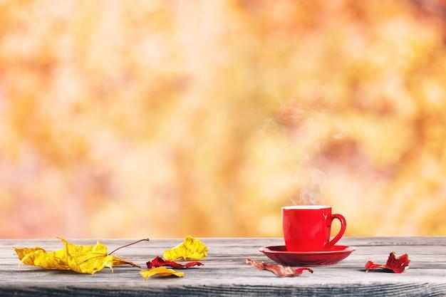 Rote tasse und herbstlaub auf dem tisch Premium Fotos