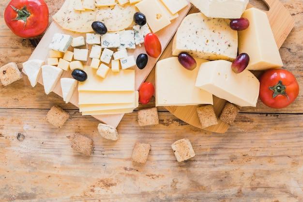 Rote tomaten, trauben, oliven und käseblöcke auf hölzernem schreibtisch Kostenlose Fotos