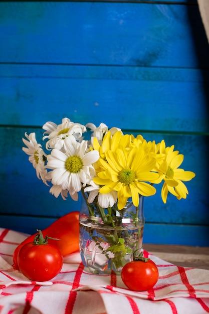Rote tomaten und eine blumenvase auf blau Kostenlose Fotos