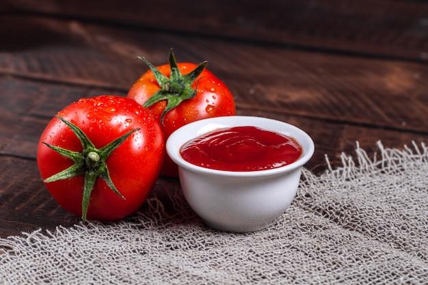 Rote tomaten und tomatensauce auf einem dunklen, hölzernen hintergrund. Premium Fotos