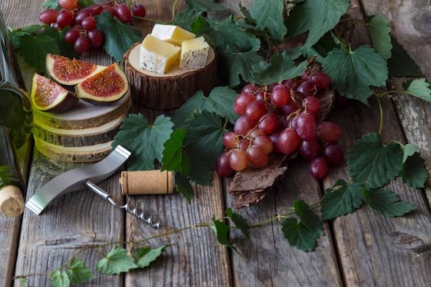 Rote trauben, eine flasche wein, ein glas, feigen und käse auf einem holzständer, eine flasche wein Premium Fotos