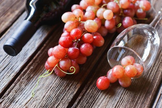 Rote trauben, glas, flasche rotwein, korken und korkenzieher Premium Fotos
