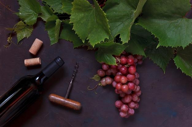 Rote trauben mit blättern, korken, korkenzieher und einer flasche rotwein. Premium Fotos