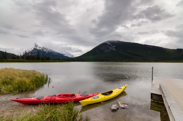 Rote und gelbe kajaks sitzen an einem dock mit blick auf den mount rundle auf die vermillion lakes Premium Fotos