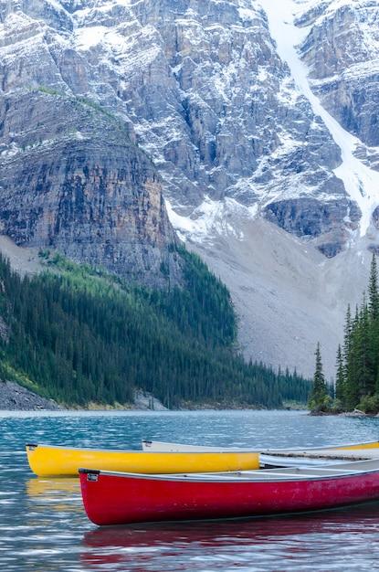Rote und gelbe kanus auf moraine lake in banff national park, kanada Premium Fotos