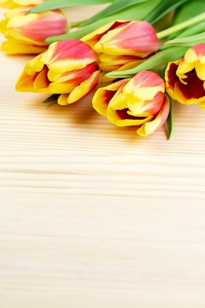 Rote und gelbe tulpen auf holzbarer nahaufnahme, kopierraum Premium Fotos