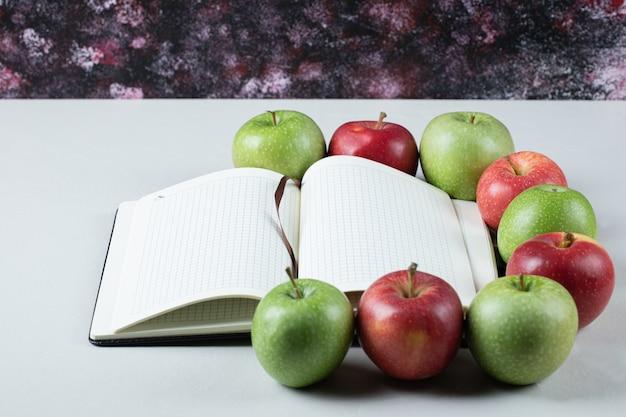 Rote und grüne äpfel mit einem leeren rezeptbuch herum Kostenlose Fotos