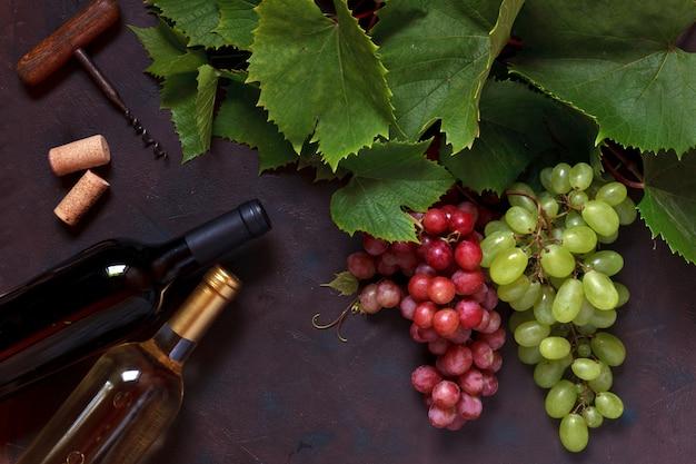 Rote und grüne trauben mit blättern, korken, korkenzieher und zwei flaschen wein, weiß und rot. Premium Fotos