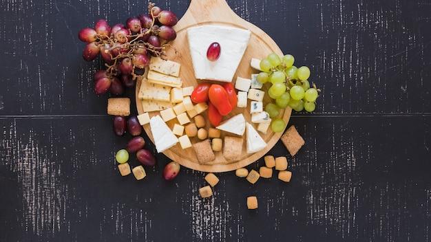Rote und grüne trauben, tomaten, käse und gebäck auf schwarzem strukturiertem hintergrund Kostenlose Fotos