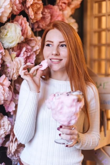 Rote vorangegangene lächelnde junge frau, welche die zuckerwatte steht gegen blumendekoration isst Kostenlose Fotos