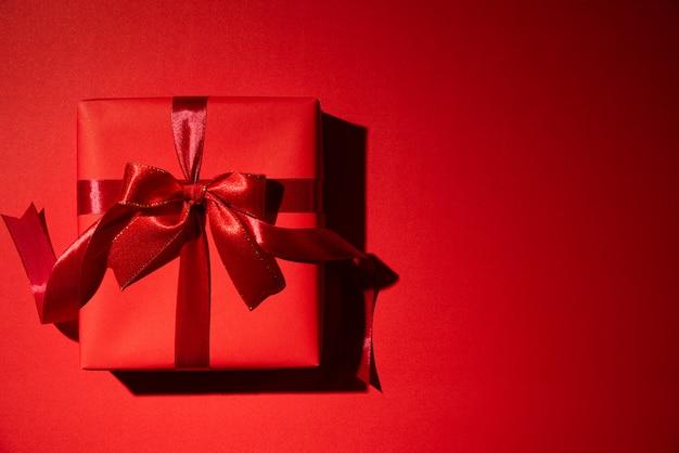 Rote weihnachtskästen auf rotem hintergrund mit copyspace für text. schwarzer freitag. Premium Fotos