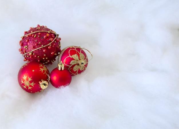 Rote weihnachtskugeln auf schneehintergrund Premium Fotos