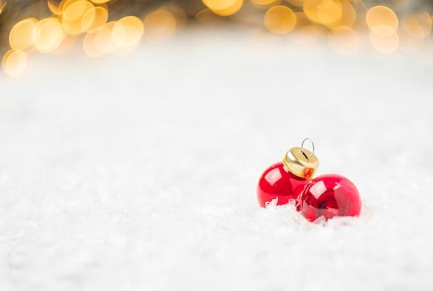 Rote weihnachtskugeln, die auf dem schnee auf dem hintergrund des weihnachtsbaumes liegen Premium Fotos