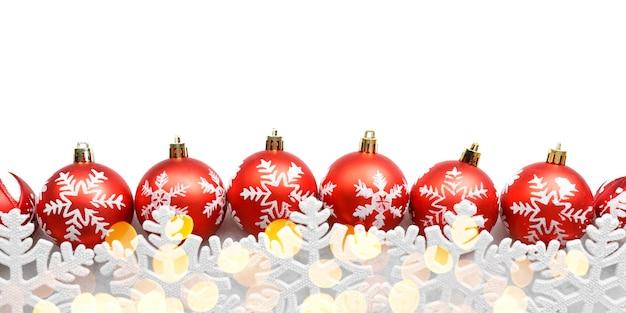 Rote weihnachtskugeln mit schneeflocken und goldlichtern lokalisiert auf weißem hintergrund Premium Fotos