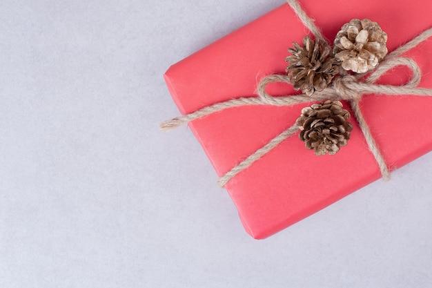 Rote weihnachtsschachtel mit drei tannenzapfen auf weißer oberfläche Kostenlose Fotos