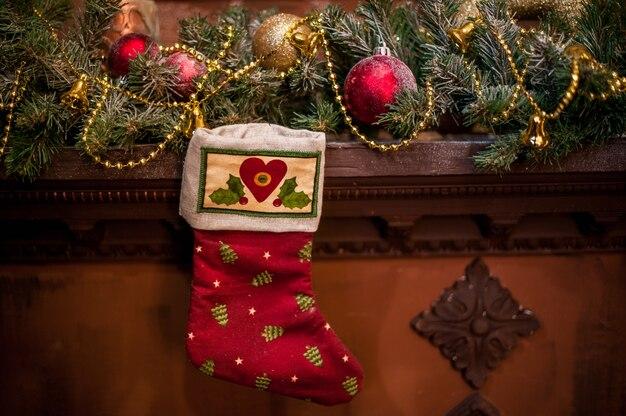 Rote weihnachtssocke, die am kamin hängt. fichtenzweige, spielzeug weihnachtsstimmung Premium Fotos