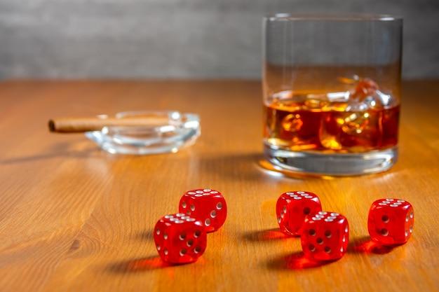 Rote würfel auf einem holztisch. glas whisky mit eiswürfeln und aschenbecher mit zigarre Premium Fotos