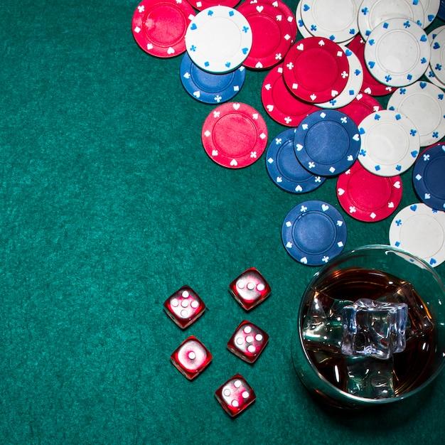 Rote würfel; kasinochips und whiskyglas auf grüner pokertabelle Kostenlose Fotos
