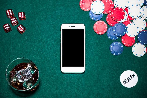 Rote würfel; whiskyglas; casino-chips; händler-chip und handy am pokertisch Kostenlose Fotos