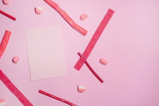 Rote zuckersüßigkeiten und lollies mit leerem blatt papier Premium Fotos