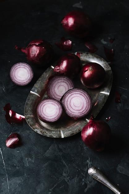 Rote zwiebeln der hohen ansicht auf einer platte und einem messer Kostenlose Fotos