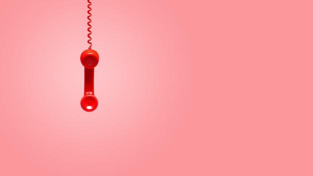 Roter alter telefonhörer, der am rosa hintergrund hängt Premium Fotos