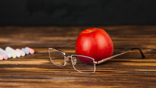 Roter apfel in der nähe von gläsern Kostenlose Fotos