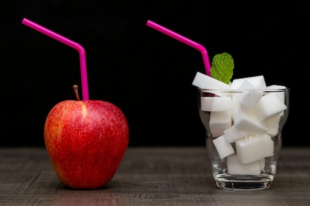 Roter apfel und cocktail mit zuckerwürfeln, wahl des zuckerkonsums Premium Fotos