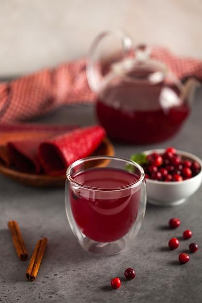 Roter beerentee ihrer preiselbeeren, schwarzer tee, zimt, ingwer und minze in einer teekanne mit einem becher und einer schüssel preiselbeeren Premium Fotos
