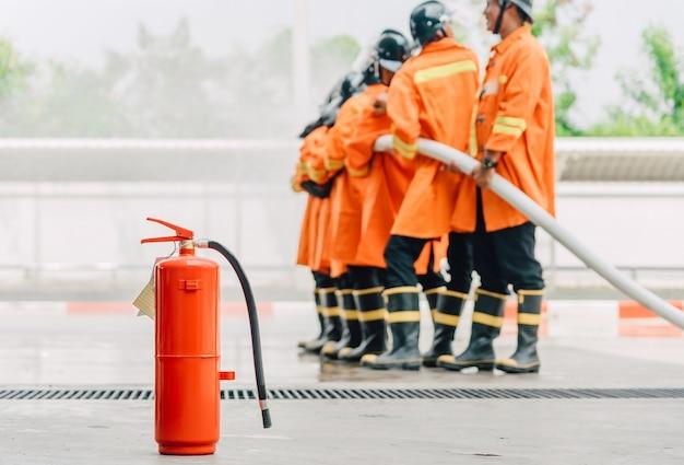 Roter behälter des feuerlöschers, vordergrund ist der feuerwehrmann, der hochdruckwasser spritzt Premium Fotos