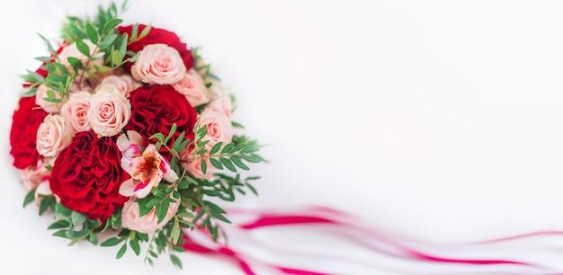 Roter blumenstrauß auf weißem hintergrund. banner zum valentinstag, hochzeit. hochzeitsstrauß mit rosen und nelken Premium Fotos