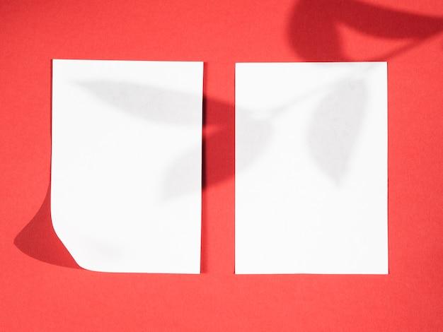 Roter hintergrund mit einem blattniederlassungsschatten auf zwei weißen decken Kostenlose Fotos
