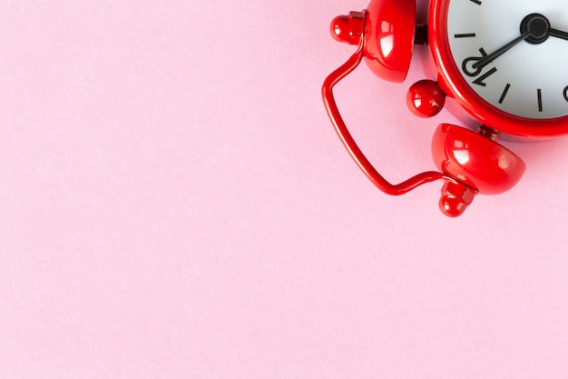 Roter kleiner wecker auf hellem pastellrosahintergrund mit copyspace. Premium Fotos