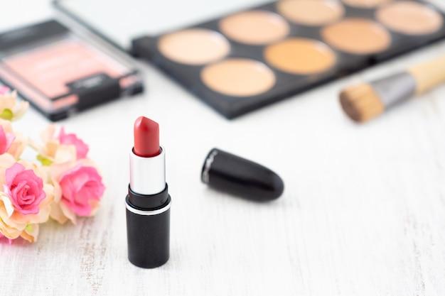 Roter lippenstift mit dekorativem kosmetiksammlungssatz. Premium Fotos