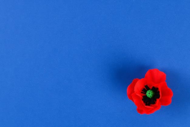 Roter mohn anzac-papiertag, erinnerung, erinnern sich, memorial day-krepppapier auf blauem hintergrund. Premium Fotos
