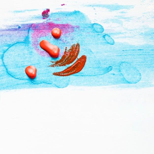 Roter nagellacktropfen und -anschlag auf befleckter blauer beschaffenheit über weißem hintergrund Kostenlose Fotos