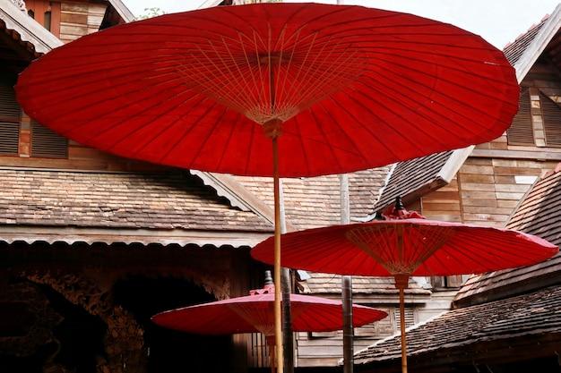Roter papierregenschirm und hölzernes haus Premium Fotos