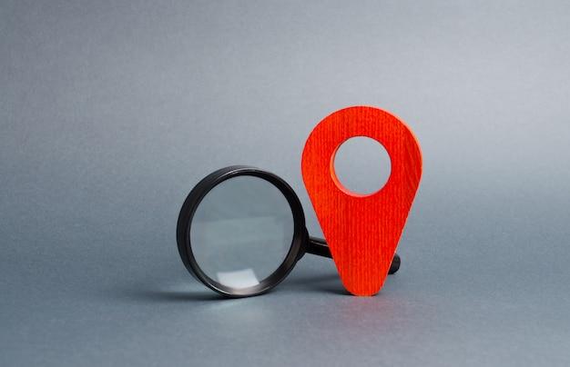 Roter positionszeiger und eine lupe auf einem grau. tourismus und reisen Premium Fotos