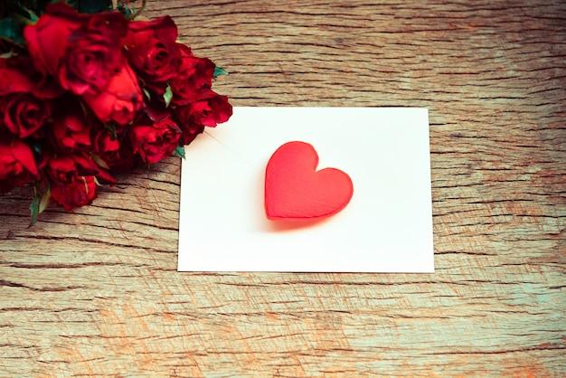 Roter rosenblumenstrauß romantische liebe valentinstagskarte umschlag briefpost mit rotem herzen Premium Fotos