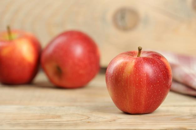 Roter saftiger apfel auf hölzernem hintergrund Premium Fotos