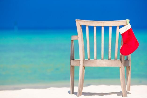 Roter sankt-hut auf stuhl am tropischen weißen strand Premium Fotos