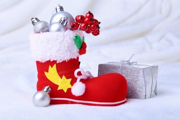 Roter sankt stiefel mit weihnachtsgeschenken auf schneehintergrund. frohe feiertage zusammensetzung. Premium Fotos