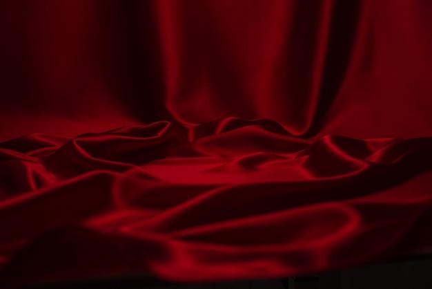 Roter seiden- oder satinluxusstoff-texturhintergrund. Premium Fotos