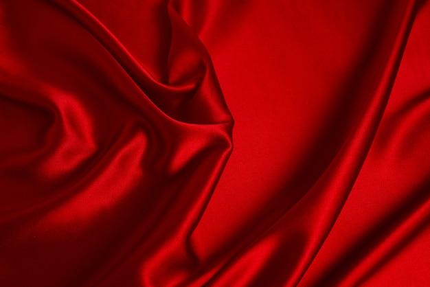 Roter seiden- oder satinluxusstoffbeschaffenheit abstrakter hintergrund Premium Fotos