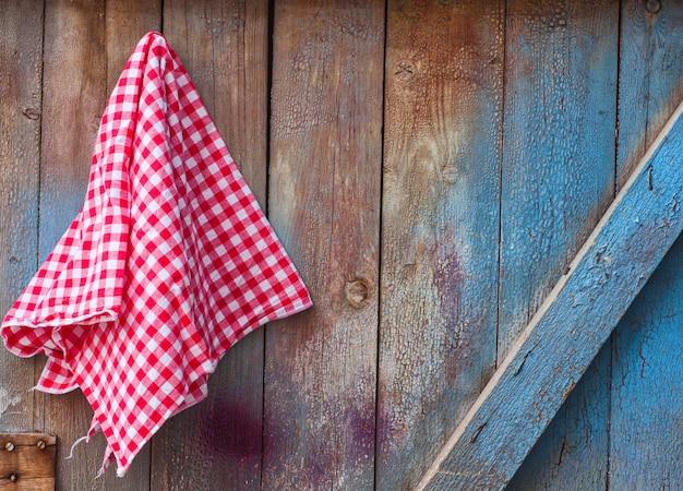Roter stoff in einer zelle, die an einer hölzernen gebrochenen wand hängt Premium Fotos