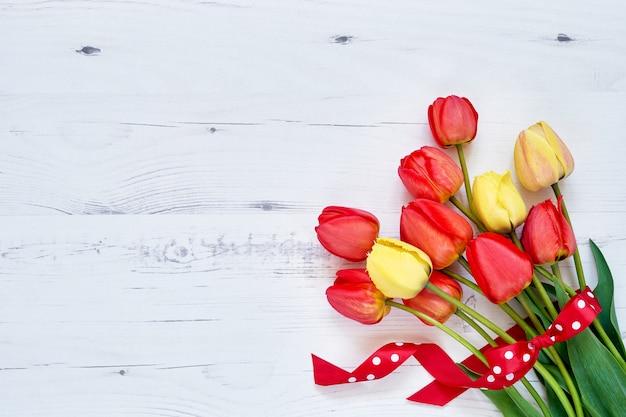 Roter tulpenblumenstrauß verziert mit band auf weißem hölzernem. Premium Fotos