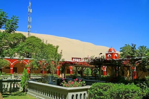 Roter turm des peruanischen gebäudes der weinlese gegen die sanddünen von huacachina-wüste, ica-region, peru Premium Fotos