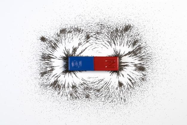 Roter und blauer stangenmagnet mit eisenpulvermagnetfeld auf weißem hintergrund. Premium Fotos